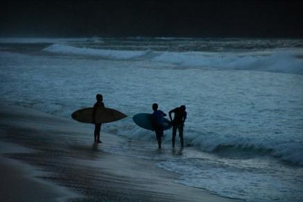 Locals fent surf fins que marxa el sol
