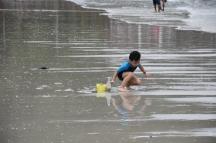 Un nen juga a la platja tot i la fina cortina de pluja