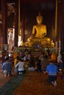 Tailandesos pregant davant del Buda