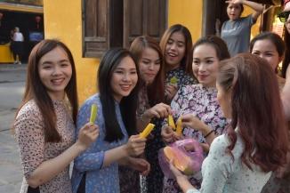 Unes noies mengen fruita a Hoi An