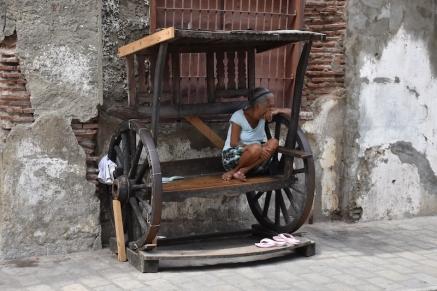 Una filipina asseguda en un banc al carrer Crisólogo