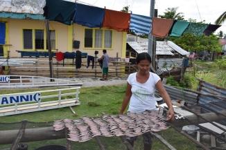 Una noia posa a secar peix