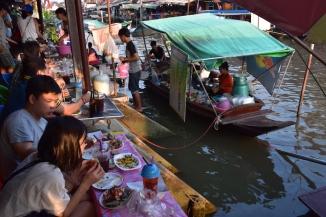 La gent seu a degustar el menjar que fan a les embarcacions