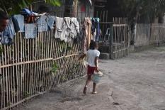 Una nena porta aigua cap a casa seva