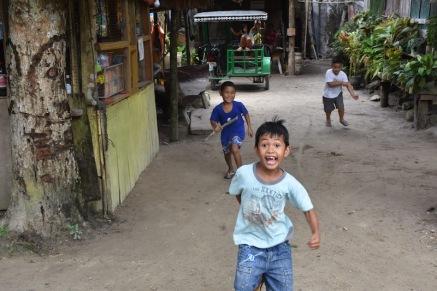 Nens jugant pels carrers de Port Barton