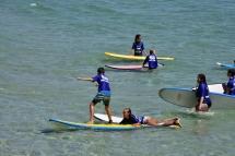 Nens aprenent a fer surf a l'escola