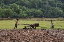 Un home i els seus fills treballant al camp a Kong Lor